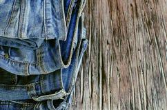 说谎在一张木桌上的堆牛仔裤 库存照片