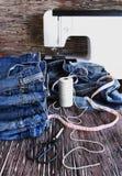 说谎在一张木桌上的堆牛仔裤 免版税库存图片