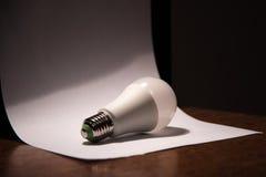 说谎在一张白色纸的白光电灯泡 免版税库存图片