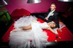 说谎在一张红色桌上的一套白色婚礼礼服的美丽的女孩演奏美国水池 免版税库存照片