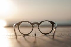 说谎在一木桌正面图sundawn的玻璃 免版税图库摄影