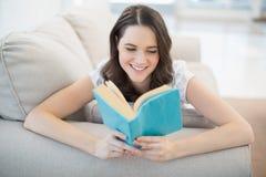 说谎在一本舒适长沙发阅读书的平安的俏丽的妇女 免版税库存图片