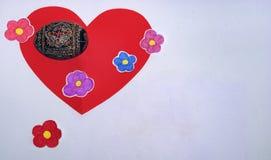 说谎在一朵红色心脏和被绘的花的被绘的鸡蛋 免版税库存图片