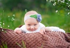 说谎在一条毯子的微笑的小女孩在公园 库存图片