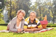 说谎在一条毯子的成熟夫妇在公园 免版税图库摄影