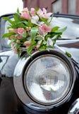 说谎在一辆老减速火箭的汽车的车灯的婚礼的花束 库存图片
