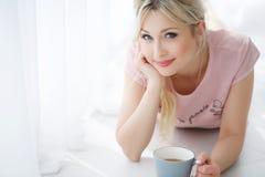 说谎在与一杯茶的一个白色地板上的美丽的妇女 库存照片