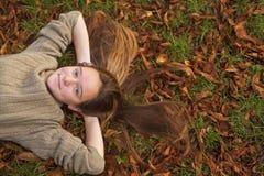 说谎在与下落的叶子的地面上的女孩在秋天公园 免版税库存照片
