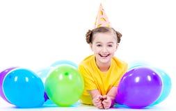 说谎在与五颜六色的气球的地板上的愉快的女孩 库存照片