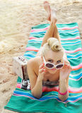 说谎在与五颜六色的葡萄酒的海滩的可爱的少妇 免版税库存照片
