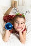 说谎在与圣诞节泡影的床上的逗人喜爱的小女孩 免版税图库摄影