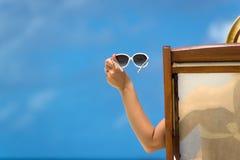 说谎在与在手中玻璃的一个海滩懒人的女孩在热带海岛上 免版税库存照片