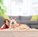 说谎在与她的爱犬的地板上的女孩 免版税库存图片