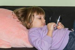 说谎在与她的被充塞的玩具猪和手机的床上的逗人喜爱的小女孩 免版税图库摄影