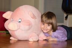 说谎在与她的被充塞的玩具猪的地板上的逗人喜爱的小女孩 库存图片
