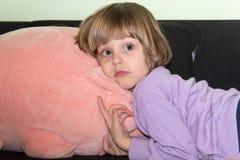 说谎在与她的被充塞的玩具猪的床上的逗人喜爱的小女孩 免版税库存照片