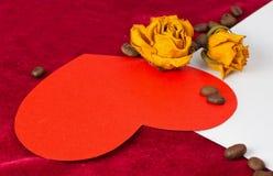 说谎在与干玫瑰和咖啡豆的一个信封的红色心脏 免版税库存照片
