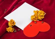说谎在与干玫瑰和咖啡豆的一个信封的红色心脏 免版税图库摄影