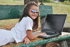 说谎在与您的计算机的一条长凳的小女孩 免版税库存照片