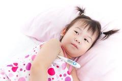 说谎在与数字体温计的病床的小女孩在她的胳膊 免版税库存图片