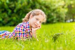 说谎在与数字式片剂的草的俏丽的少年女孩 库存图片