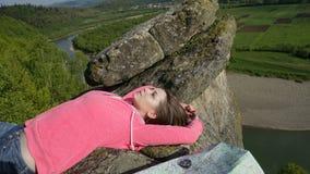 说谎在与旅行的岩石的年轻旅游妇女归因于:指南针,地图 库存照片