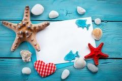 说谎在与明信片的蓝色木背景的海星、小卵石和壳 有标签的一个地方 免版税库存照片