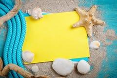 说谎在与明信片的蓝色木背景的海星、小卵石和壳 有标签的一个地方 图库摄影