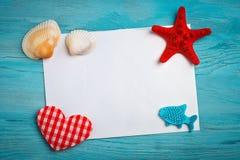 说谎在与明信片的蓝色木背景的海星、小卵石和壳 有标签的一个地方 免版税库存图片