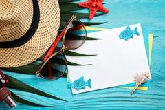 说谎在与明信片的蓝色木背景的海星、小卵石和壳 有标签的一个地方 库存照片