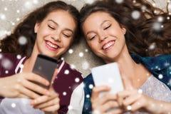 说谎在与智能手机的地板上的愉快的十几岁的女孩 库存照片