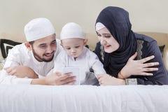 说谎在与智能手机的床上的回教家庭 免版税库存图片
