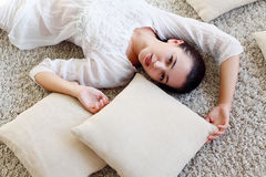 说谎在与枕头的地板上的女孩 库存照片