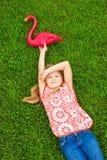 说谎在与桃红色火鸟的绿草的微笑的小女孩 库存照片