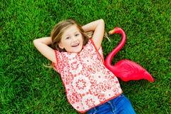 说谎在与桃红色火鸟的绿草的微笑的小女孩 免版税库存照片