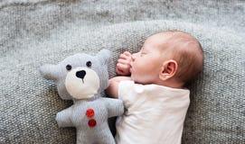 说谎在与玩具熊的床上的新出生的男婴,睡觉 免版税库存图片