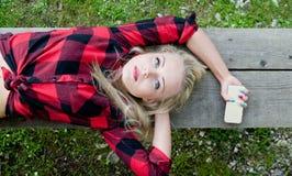 说谎在与电话的一条长凳的妇女 库存图片