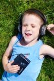 说谎在与老卡型盒式录音机球员的草的小男孩 免版税库存照片