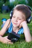 说谎在与老卡型盒式录音机球员的草的小男孩 免版税图库摄影
