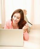 说谎在与膝上型计算机的地板上的一个少妇 免版税库存照片