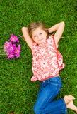 说谎在与花的绿草的微笑的小女孩 免版税库存照片