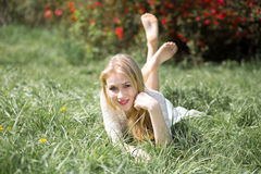 说谎在与被举的腿的草的白肤金发的少妇 女孩可爱微笑和享用的开花在春天 库存照片