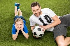 说谎在与足球的草的父亲和儿子 库存图片
