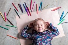 说谎在与闭合的眼睛的地板纸的孩子临近蜡笔 小女孩绘画,图画 顶视图 大厦概念创造性墙壁的现有量lego 免版税库存图片