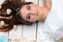 说谎在与贝壳的地板上的美丽的女孩在她的头发 画象 工作室 免版税库存图片