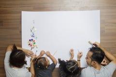 说谎在与绘画的地板上的顶视图愉快的家庭 免版税图库摄影