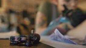说谎在与yong tattooer妇女backgroung的桌上的纹身花刺机器在演播室运转在客户` s腿的图画 影视素材