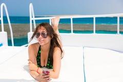 说谎在举行她的pho的游艇的甲板的泳装的妇女 库存图片