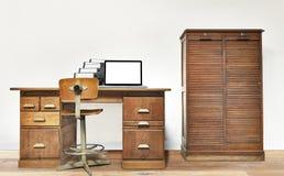 说谎在书桌上的膝上型计算机和文件夹 免版税库存图片
