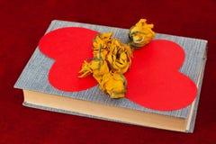 说谎在书的五朵黄色玫瑰和两红色纸心脏 免版税库存照片